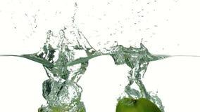 Apple parte en dos el hundimiento en el agua en el fondo blanco metrajes