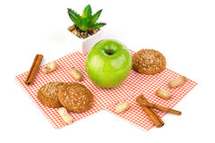 Apple, peanuts and oatmeal cookies on a white table. Apple, peanuts, oatmeal cookies and aloe flower Stock Photography