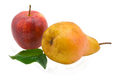 Apple and pear. Red apple, a yellow pear and green sheet the isolated Royalty Free Stock Photography