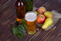 Apple and pear cider glass and bottles with fruits. Royalty Free Stock Image