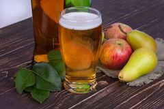 Apple and pear cider glass and bottles with fruits. Stock Image