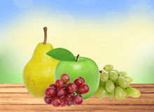 Apple, pear and grape on wooden table over blurred nature Stock Image
