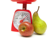 Apple, pear and kitchen scale on white background Royalty Free Stock Image