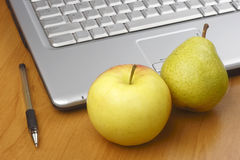 Apple,pear,pen and laptop Royalty Free Stock Photo