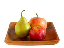 Apple, pear and plum on a wooden plate Stock Photo