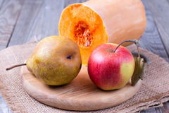 Apple, pear and pumpkin on a wooden background Stock Image