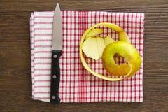 Apple peel med kniven på den röda ginghamhandduken Arkivfoton