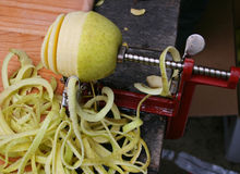 Apple Peeler with Half-Peeled Apple Royalty Free Stock Images
