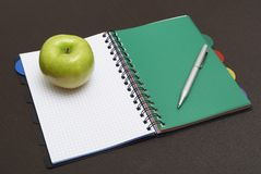 Apple, pen on spiral notebook Stock Photos