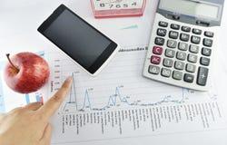 Apple, pengar, klocka, telefon och räknemaskin som förläggas på dokument Arkivbild