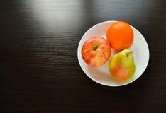 Apple, pera, mentira anaranjada en una placa blanca foto de archivo