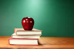 Apple più la pila di libri su uno scrittorio per di nuovo alla scuola Immagini Stock Libere da Diritti