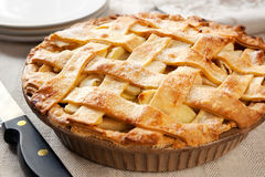 Apple Pie. Home-baked lattice apple pie, in a brown ceramic pie plate, ready to serve Royalty Free Stock Image