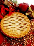 Apple pie. Hot apple pie with apples, poinsettias, cinnamon sticks in the background Stock Photography