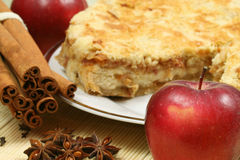Apple and pie. Delicious red apple in the foreground and cinnamon sticks with apple pie in background Royalty Free Stock Images