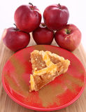 Apple Pie. A slice on a plate decorated with cinnamon and some red apples royalty free stock photography
