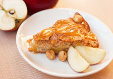Apple pie. Tasty fresh apple pie with slices of apple and hazelnuts covered with honey on a white plate on a kitchen table Stock Photography