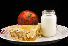Apple Pie. Large slice of apple pie captured on a plate with apple and jar of milk on a black background stock photo