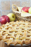 Apple Pie. Baked apple lattice pie with wicker basket and apples behind Stock Images