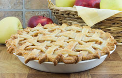 Apple pie. Lattice apple pie with wicker basket and apples behind Royalty Free Stock Photos