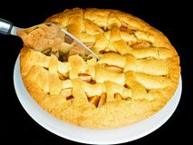 Apple pie American style. Closeup of apple pie, a traditional American dessert , with silver cake slicer about to cut a piece, black background royalty free stock images