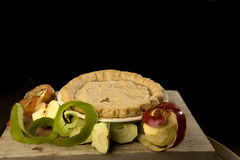 Apple pie with apples. Apple pie with peeled fresh apples on a cutting board Royalty Free Stock Photo