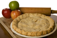 Apple pie with apples. Apple pie with slice of apple pie on plate with fork and rolling pin and recipe book Stock Images