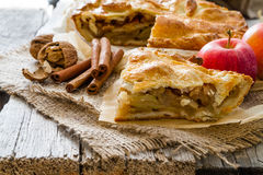 Apple pie with apples, cinnammon and nuts. Rustic wood background, copy space Stock Images