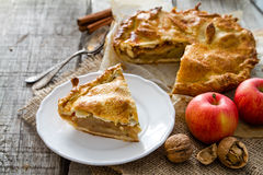 Apple pie with apples, cinnammon and nuts. Rustic wood background, copy space Royalty Free Stock Images