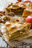 Apple pie with apples, cinnammon and nuts. Rustic wood background, copy space Royalty Free Stock Photo