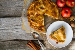 Apple pie with apples, cinnammon and nuts. Rustic wood background, copy space, top view Stock Images