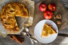 Apple pie with apples, cinnammon and nuts. Rustic wood background, top view Royalty Free Stock Photos