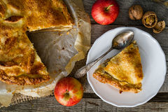 Apple pie with apples, cinnammon and nuts. Rustic wood background, top view Stock Photography