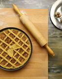Apple pie in baking tray, wooden rolling pin Stock Image