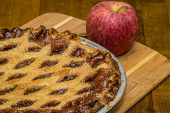 Apple Pie. On bamboo cutting board next to a big red apple Royalty Free Stock Photos