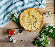 Apple pie with a blossom branch on table. Rustic and summer mood Royalty Free Stock Photo