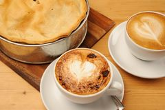 Apple Pie and Cappuccino Coffee. Freshly baked Apple Pie and a cup of cappuccino coffee on a wooden restaurant table royalty free stock photography