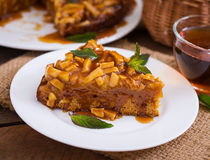 Apple pie with caramel sauce. On a wooden background stock image