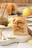 Apple pie with cinnamon. Piece of apple pie and caramel on a white board with a wooden knife Royalty Free Stock Photos