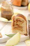 Apple pie with cinnamon. Piece of apple pie and caramel on a white board with a wooden knife Royalty Free Stock Image