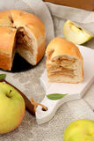 Apple pie with cinnamon. Piece of apple pie and caramel on a white board with a wooden knife Royalty Free Stock Photo
