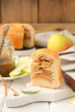 Apple pie with cinnamon. Piece of apple pie and caramel on a white board with a wooden knife Stock Images