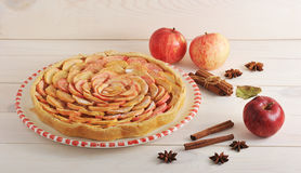 Apple pie with cinnamon on a plate and apples and cinnamon Royalty Free Stock Images