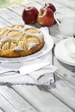 Apple pie, coffee cup and plate, apples on wood Royalty Free Stock Image