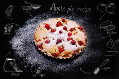 Apple pie with cranberry and drawing recipe on black table Royalty Free Stock Photo
