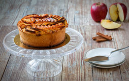 Apple pie on crystal cake plate on wooden table Royalty Free Stock Image