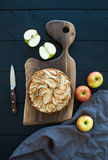 Apple pie on dark chopping board over black wooden Royalty Free Stock Photo