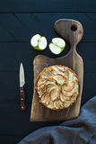 Apple pie on dark chopping board over black wooden Royalty Free Stock Images