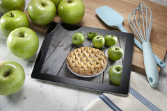 Apple Pie Dessert Computer Tablet. A computer tablet or digital cookbook with an apple pie dessert on the screen. surrounded by apples cutting board and kitchen Royalty Free Stock Photography