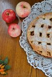 Apple pie in a dish next to the apples and the tablecloth Stock Photo